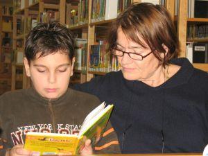 Frau Deus liest mit einem Kind ein Buch